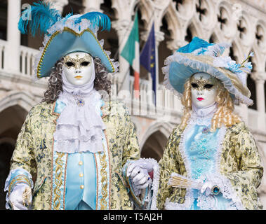 Couple dressed in traditional Venetian masks and costume, Doge's Palace (Palazzo Ducale), Venice carnival, Italy - Stock Photo