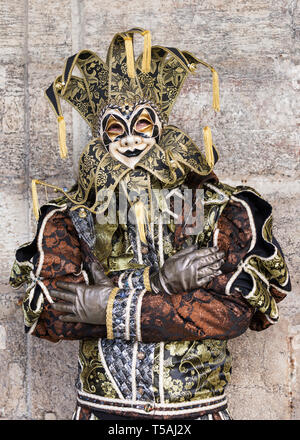 Man wearing jester costume and harlequin mask, Venice carnival, Italy - Stock Photo