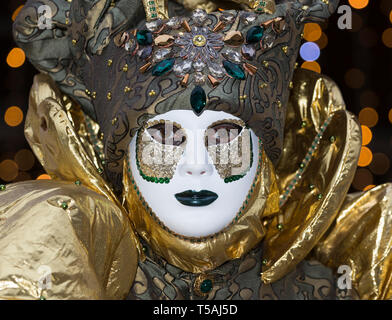 Venice carnival portrait, Italy, adult man wearing white mask and gold costume, close up - Stock Photo