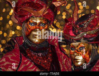 Venice carnival couple wearing fire masks and red costumes, Italy, night portrait with bokeh lights background - Stock Photo