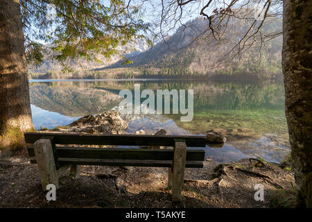 Empty wooden bench at the shore of the Vorderer Langbathsee near Ebensee, OÖ, Austria, with the great landscape reflecting on the crystal clear water - Stock Photo