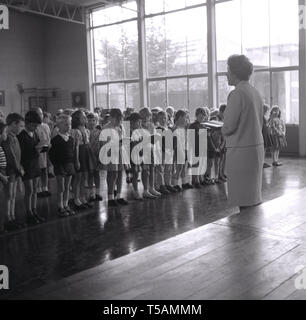 1960s, historical, headmistress reading a passage from a book - possibly the bible - to a group of  primary school children standing in a line at morning assembly, England, UK. - Stock Photo
