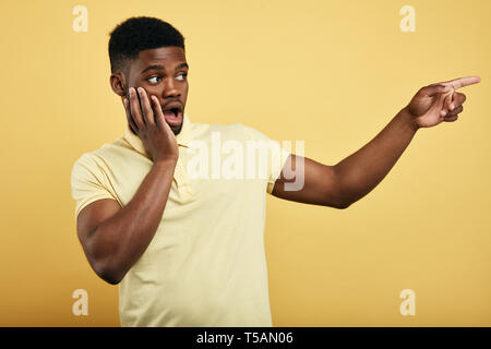 astonished emotional young dark-skinned man dressed in stylish T-shirt,touching his cheek, pointing at copy space on yellow wall for text. guy is afraid of somebody, close up portrait
