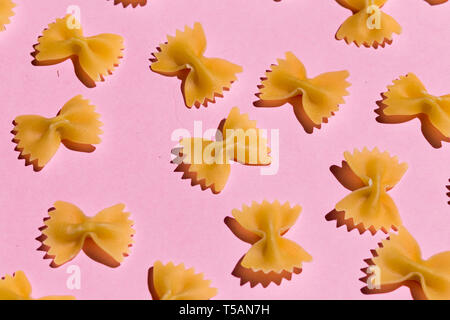 bow tie pasta isolated on pink background. top view - Stock Photo
