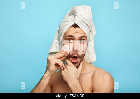 delighted crazy man holding a cotton pad while caring about his skin. close up portrait. - Stock Photo