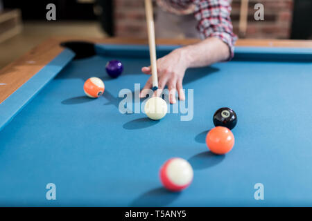 Close up shot of hipster guy aiming the billiards ball. - Stock Photo