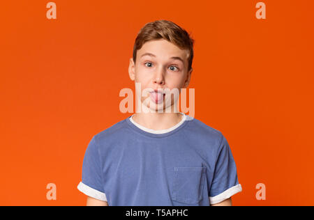 Teenage boy joking, sticking tongue out with silly expression - Stock Photo