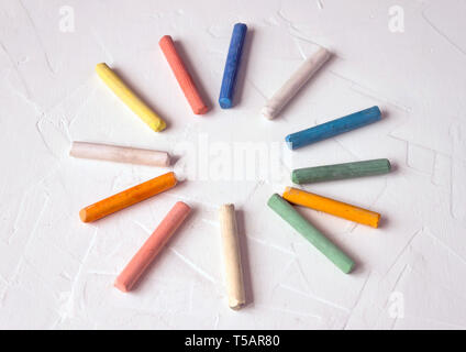 row of mixed color of used chalk pastel sticks crayon sun rays circle isolated on white background. Selective soft fokus. - Stock Photo