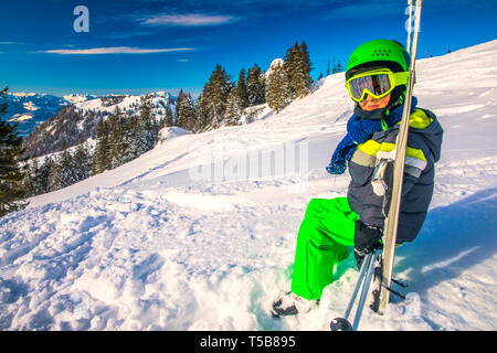 Child ready for skiing famous Ski resort in Alps. - Stock Photo