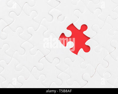 White blank jigsaw puzzle without one piece on red. Clipping path on the missing piece. Missing part, organization and solution theme - Stock Photo