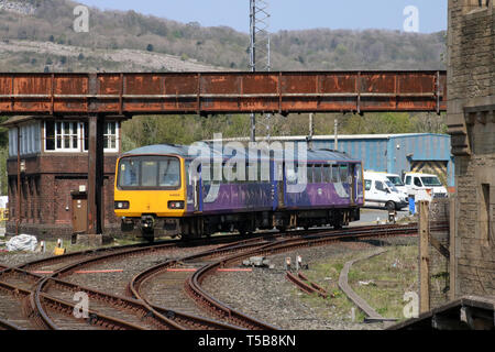 Two car class 144 Pacer diesel multiple unit passenger train in Northern livery leaving Carnforth railway station on 22nd April 2019. - Stock Photo