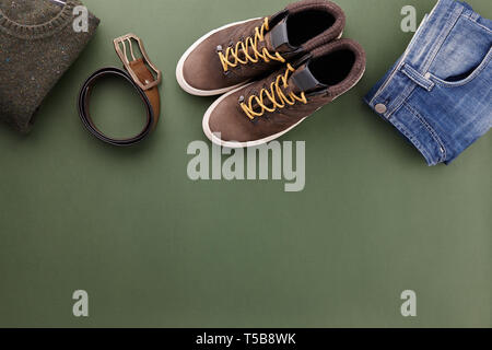 Mens fall casual clothing outfits and accessories flat lay on olive green background, top view - Stock Photo