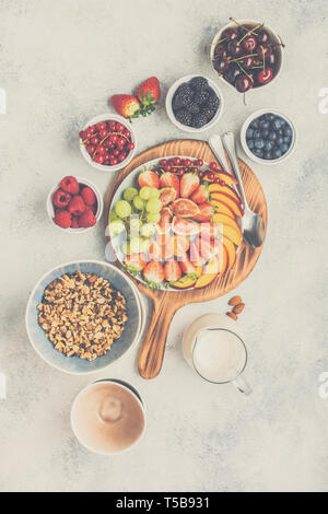 Raw vegan grain free paleo style granola or muesli made from nuts. Fruit berries platter, strawberries blueberries raspberries peach figs red currant, overhead view, toned, selective focus - Stock Photo