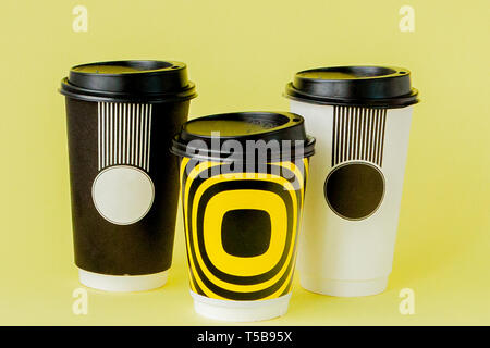 Take-out coffee in thermo cup on a yellow background. - Stock Photo