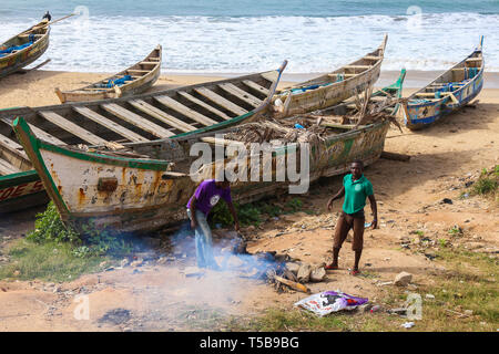 Two men cook a dog on the beach in Cape Coast, Ghana. - Stock Photo