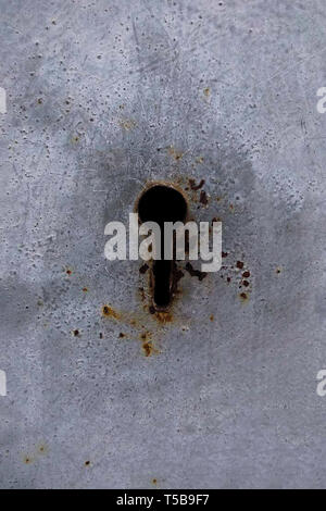 detail of an old lock on a wooden door. Old lock on a weathered wooden door. Keyhole in an old paneled wooden door rusty and weathered - Stock Photo