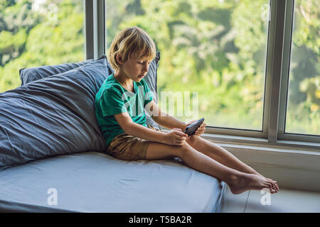 Little blond boy playing games on smartphone - Stock Photo