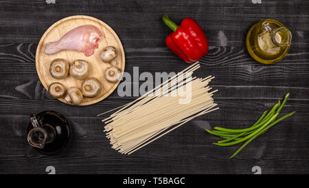 Fresh ingredients for cooking home-made fried noodles on a black rustic wooden table. Top view. - Stock Photo