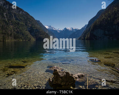 Several rocks and stones in the crystal clear water of the Königssee in Berchtesgaden - Stock Photo