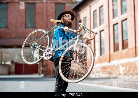 Lifestyle portrait of a bearded hipster dressed stylishly with hat and jacket carrying his retro bicycle on the urban background