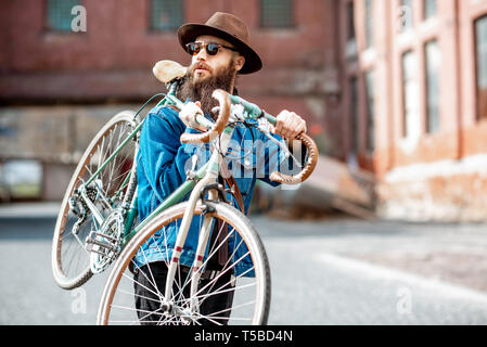 Lifestyle portrait of a bearded hipster dressed stylishly with hat and jacket carrying his retro bicycle on the urban background - Stock Photo