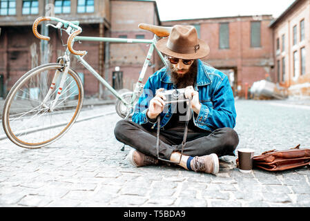 Bearded hipster dressed stylishly with hat and jacket sitting with photo camera and retro bicycle on the street outdoors - Stock Photo
