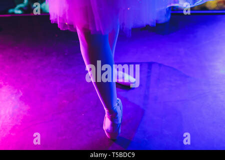 Ballerina legs in pointes on parquet floor on dark background. - Stock Photo
