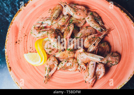 fried roasted shrimps in plate with lemon greens parsley garlic. - Stock Photo