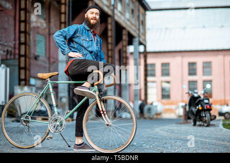 Portrait of a bearded man as a crazy hipster having fun with retro bicycle outdoors on the industrial urban background Stock Photo