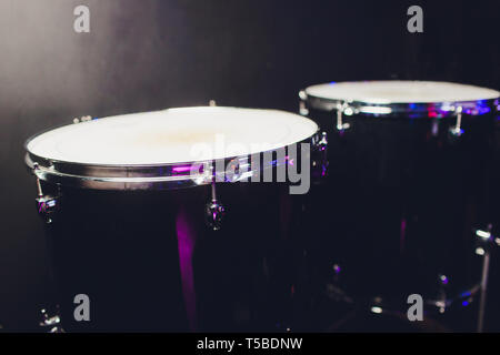drum set on dark background. Percussion instruments at a concert. Drum and plates are on the stage of the concert hall, dark background. - Stock Photo