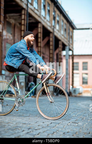 Stylish man as a crazy hipster having fun, riding retro bicycle outdoors on the industrial urban background Stock Photo
