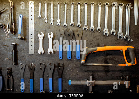 Wall with different working tools and wrenches for bicycle repairing - Stock Photo