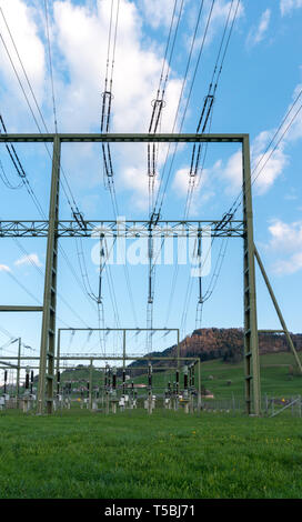 vertical view of a large high voltage power station in the hills of Switzerland supplies the backcountry with electricity - Stock Photo