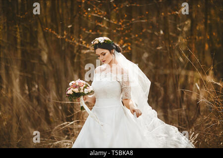 Elegant and young brunette woman with bright makeup and with a floral wreath on her head in a stylish wedding dress with a bouquet of flowers outdoors - Stock Photo