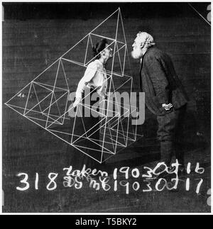 Alexander Graham Bell (1847-1922) facing his wife, Mabel Hubbard Gardiner Bell, who is standing in a tetrahedral kite, 1902 - Stock Photo
