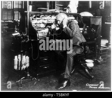 Thomas Edison (1847-1931) at his desk, talking on telephone, showing a wax cylinder dictating machine and cylinders, 1914 - Stock Photo