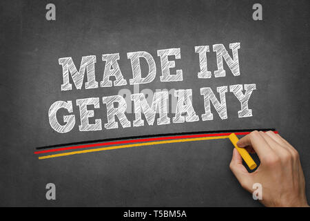 hand writing MADE IN GERMANY on chalkboard - underlining with colours of german flag - Stock Photo