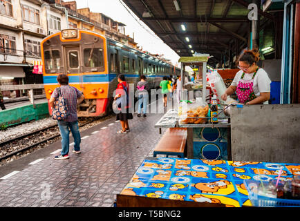 Thonburi station, Bangkok - March 14, 2019: Commuters waits to board the train where they can buy food to take away or eat directly on the platform. - Stock Photo