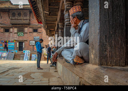 BHAKTAPUR, NEPAL - APRIL 5, 2019: Old man with traditional nepalese hat staring at passers-by - Stock Photo