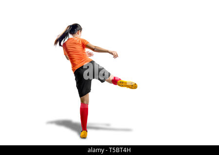 Rear view of asian football player woman in orange jersey with kicking the ball position isolated over white background - Stock Photo