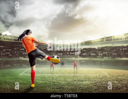 Rear view of asian football player woman in orange jersey kicking the ball on the football field at stadium - Stock Photo