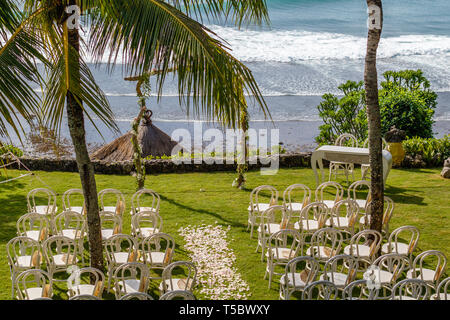 Wedding arch for a ceremony decorated with fresh flowers, chairs and sun umbrellas for guests among palm trees near the ocean. Tropical wedding. - Stock Photo