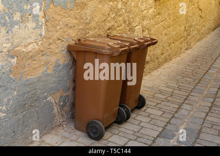 Brown dustbins in front of a wall of a house - Stock Photo