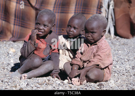 Namibia. Himba tribe village. Children sitting outside. - Stock Photo