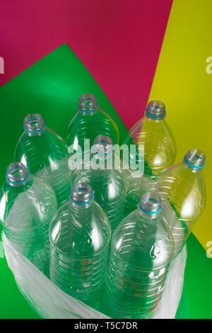 A pack of 8 empty and recyclable plastic water bottles, with no caps, blue seal, in a plastic bag, on a geometrical colored vibrant sea green, wine - Stock Photo