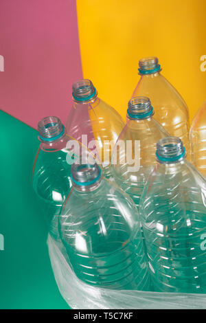 A pack of 7 empty and recyclable plastic water bottles, with no caps, blue seal, in a plastic bag, on a colored pastel tones of sea green, soft pink - Stock Photo