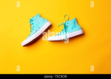 Pair of stylish sneakers laing on yellow background - Stock Photo