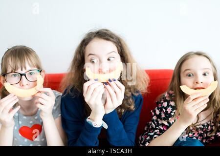 Three young girls sitting on red sofa and eating yellow melon - making big smile emoticon. - Stock Photo