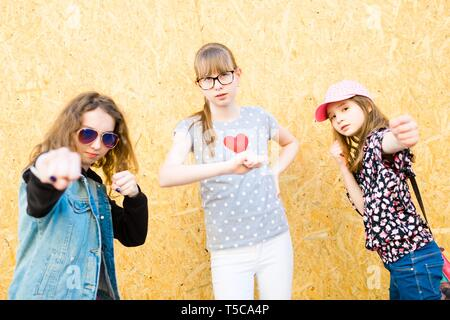 Three young girls posing in front of a wooden wall - showing fight poses - fun in the city - Stock Photo