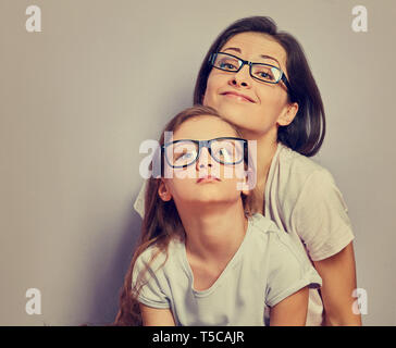 Grimacing positive smiling casual mother looking sitting with her unhappy offended thinking kid girl on violet wall background. Family in fashion eye  - Stock Photo